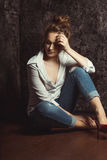 Tender young woman in shirt and jeans sitting on the floor Royalty Free Stock Photography