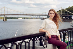 Tender young woman sitting on the pier Stock Image