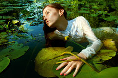 Tender young woman swimming in the pond among water lilies Royalty Free Stock Photo