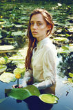 Tender young woman swimming in the pond among water lilies Royalty Free Stock Photos