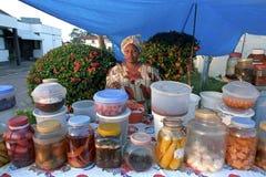 Tendera del mercado en su parada del mercado imagen de archivo