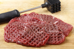 Tenderized raw minute steaks. Three raw minute steaks displayed next to a meat mallet after being pounded and tenderised stock photography