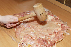 Tenderizing the meat with mallet on the kitchen board. Detail Stock Photography