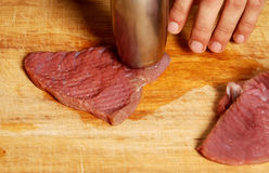 Tenderizing red meat on the kitchen board Royalty Free Stock Images