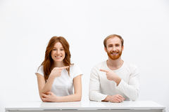 Tenderless funny redhead girl and boy sitting at white desk Stock Images