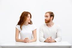 Tenderless redhead girl and boy sitting at white desk Stock Image