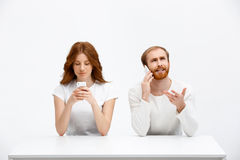 Tenderless redhead girl and boy talking on phones  chatting a. Beautiful redhead girl and boy sitting at the white table. Isolated at the white background. Girl Stock Image