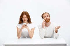 Tenderless redhead girl and boy talking on phones  chatting a. Beautiful redhead girl and boy sitting at the white table.  at the white background. Girl chatting Stock Image