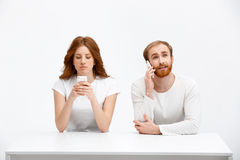 Tenderless redhead girl and boy talking on phones  chatting a. Beautiful redhead girl and boy sitting at the white table.  at the white background. Girl chatting Stock Photo