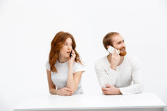 Tenderless redhead girl and boy talking on phones  sitting at. Beautiful redhead girl and boy sitting at the white table and talking on phones. Isolated at the Stock Photo