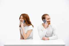 Tenderless redhead girl and boy talking on phones  sitting at. Beautiful redhead girl and boy sitting at the white table and talking on phones. Isolated at the Stock Photos