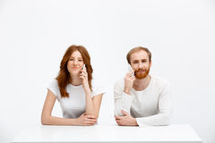 Tenderless redhead girl and boy talking on phones  sitting at. Beautiful redhead girl and boy sitting at the white table and talking on phones. Isolated at the Stock Photography