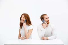 Tenderless redhead girl and boy talking on phones  sitting at. Beautiful redhead girl and boy sitting at the white table and talking on phones. Isolated at the Royalty Free Stock Photography