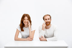 Tenderless redhead girl and boy talking on phones  sitting at. Beautiful redhead girl and boy sitting at the white table and talking on phones.  at the white Stock Photo
