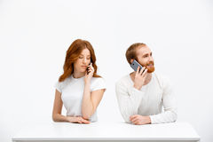 Tenderless redhead girl and boy talking on phones  sitting at. Beautiful redhead girl and boy sitting at the white table and talking on phones.  at the white Stock Images