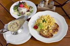 Tenderlion свинины служило на плите с Spätzle и champignons смешанным салатом и соусом Стоковые Фото