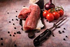 Tenderloin свинины и другие ингридиенты на винтажной доске Стоковые Изображения RF