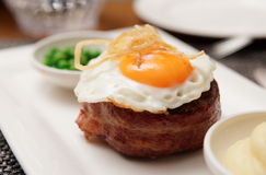 Tenderloin steak with fried egg and green pies Stock Photography