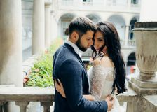 Tenderly hugging newlywed couple standing head-to-head on the balcony of the old building. Tenderly hugging newlywed couple standing head-to-head on the balcony Royalty Free Stock Photos
