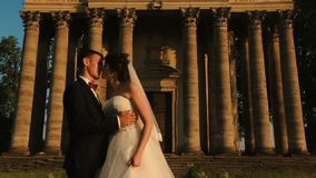 Tenderly kissing couple of attractive happy newlyweds over the background of old baroque style building during the. Sunset stock video