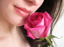 Tenderness. Close-up of female lips with pink rose Royalty Free Stock Images
