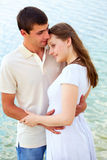 Tenderness. Photo of peaceful couple enjoying being together with blue water on background stock photography