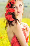 Tenderness. Girl standing with poppies in her hair Royalty Free Stock Image