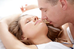 Tenderness. Close-up of a men kissing his girlfriend lying in bed Royalty Free Stock Photo