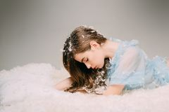 Tenderness and fragility of youth concept. Side view teenage girl lying on drowsy bed on gray background. Beautiful. Young fairy in blue dress with delicate stock image