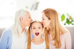 Tenderness gentle close relations concept. Portrait of beautiful. Charming lovely cute touching kid with ponytail granny mum kissing head at home indoors inside Stock Images