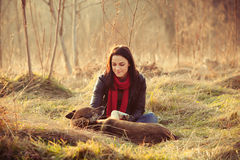 Tenderness. Girl with pariah dog sit in yellow grass warm winter day retro colors Stock Image