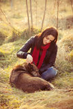 Tenderness. Girl with pariah dog sit in yellow grass warm winter day retro colors Royalty Free Stock Photo