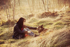 Tenderness. Girl with pariah dog sit in yellow grass warm winter day retro colors Stock Images
