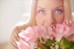 Tenderness of spring. Portrait of lovely lady looking at camera while smelling pink flowers Royalty Free Stock Photography