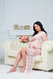 Tenderness waiting child. Expectant mother looking at pregnant belly Stock Images