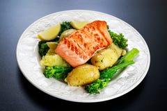 批评油煎的三文鱼服务用土豆和tenderstem硬花甘蓝 免版税库存图片