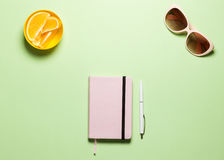 Tendez à plat le Tableau féminin d'espace de travail de configuration avec Rose Diary, stylo blanc, les lunettes, oranges sur la  Photo stock