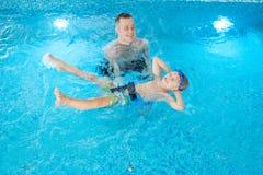 Tendo o divertimento durante a lição da natação imagem de stock