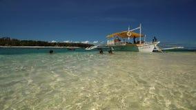 Tendo o divertimento perto do barco da guiga na praia branca da areia, Filipinas vídeos de arquivo
