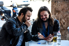 Tendo um fumo com uma cerveja que verifica para fora algo no Internet Imagem de Stock Royalty Free