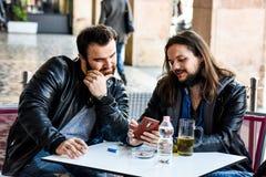 Tendo um fumo com uma cerveja que verifica para fora algo no Internet Foto de Stock Royalty Free