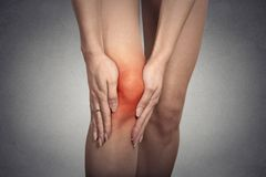 Tendon knee joint problems on woman leg indicated with red spot Stock Image