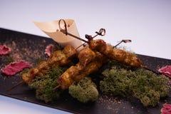 Tendones y salsa fritos del pollo en el plato blanco con el fondo de madera Imagen de archivo