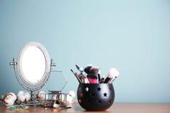 Tenedor con los cepillos y el espejo profesionales del maquillaje Foto de archivo