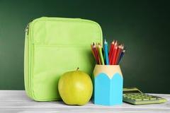 Tenedor con los lápices coloridos, el bolso del almuerzo y la manzana verde apetitosa en la tabla de madera Fotos de archivo