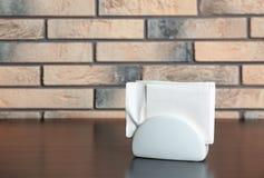 Tenedor de cerámica de la servilleta con las servilletas de papel en la tabla cerca de la pared de ladrillo imagen de archivo libre de regalías