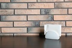 Tenedor de cerámica de la servilleta con las servilletas de papel en la tabla cerca de la pared de ladrillo imágenes de archivo libres de regalías