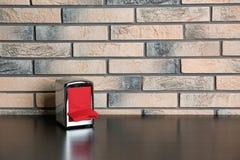 Tenedor de la servilleta con las servilletas de papel en la tabla cerca de la pared de ladrillo foto de archivo libre de regalías
