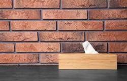 Tenedor de la servilleta con las servilletas de papel en la tabla contra la pared Espacio para el texto imagen de archivo libre de regalías