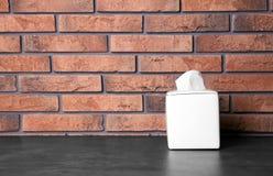 Tenedor de la servilleta con las servilletas de papel en la tabla contra la pared de ladrillo foto de archivo libre de regalías